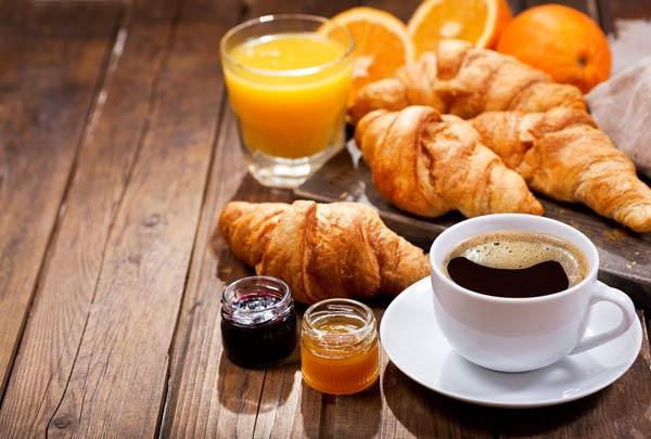 Croissants, Marmelade, Kaffee und Orangensaft auf einem Holztisch